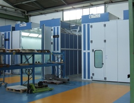 Pressurized oven booths with dry filtering system and upper openings for inserting pieces with overhead crane