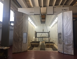 Pressurized oven booth with upper opening for inserting containers with overhead crane